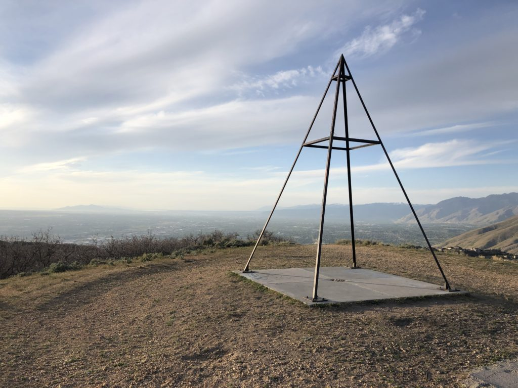 A pyramid shaped survey landmark structure in front of the mountain landscape